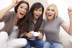 打电子游戏的美丽的妇女朋友 免版税库存图片