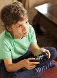 打电子游戏的逗人喜爱的男孩 免版税库存图片