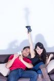 打电子游戏的年轻逗人喜爱的夫妇 免版税库存照片