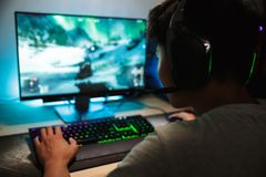 打电子游戏网上o的亚裔少年游戏玩家男孩画象  免版税图库摄影
