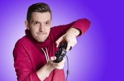 打电子游戏,紫色背景的年轻成人 免版税库存照片