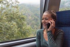 打电话与他的智能手机的年轻女人在火车的一次旅途期间,当她工作时 免版税库存照片