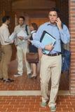 打电话与他的智能手机的可爱的成熟学生 免版税库存图片
