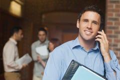 打电话与他的智能手机的可爱的男性成熟学生 免版税图库摄影