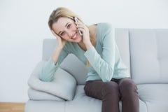 打电话可爱的偶然的妇女,当坐长沙发时 免版税库存照片