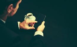 打电话和一杯咖啡在一个商人的手上在暗色的 免版税库存图片