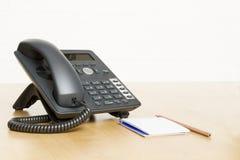 打电话在有笔记薄的书桌上在木书桌上 免版税图库摄影