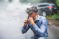 打电话在车祸以后,烟的成熟人在背景中 免版税库存照片