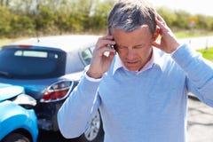 打电话的司机在交通事故以后 免版税库存图片