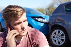 打电话的司机在交通事故以后 免版税图库摄影