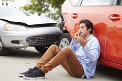打电话的少年司机在交通事故以后 库存图片