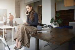 打电话的年轻女实业家,当坐办公桌和工作时 免版税库存图片