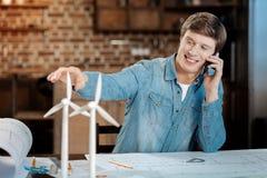 打电话的年轻工程师,当工作在图纸时 免版税库存图片