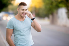 打电话的愉快的人在城市街道 库存图片