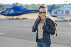 打电话的柏油碎石地面的女性直升机飞行员 图库摄影