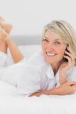 打电话的白肤金发的妇女说谎在床 库存图片