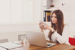 打电话的美丽的年轻女实业家由手机 免版税库存照片