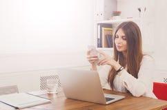 打电话的美丽的年轻女实业家由手机 免版税库存图片