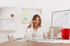打电话的美丽的年轻女实业家由手机 免版税图库摄影