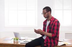 打电话的年轻黑商人在机动性在现代白色办公室 免版税库存照片
