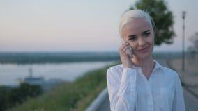 打电话的年轻美丽的女商人户外在日落 免版税库存图片