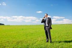 打电话从一个绿色领域的商人 库存图片