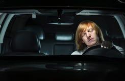 打瞌睡年轻的人,当驾驶在晚上时 免版税库存图片