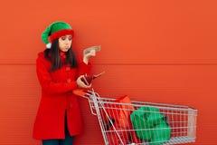 打破了花她的前美元的妇女在圣诞节购物上 库存照片
