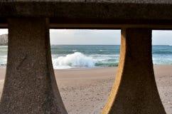 打破反对与日落光的一个海滩的波浪 看法通过在散步的扶手栏杆 La拉科鲁尼亚,西班牙,秋天风暴 库存照片