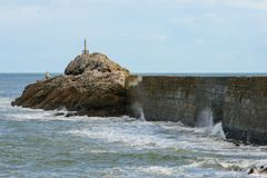 打破在一个港口的墙壁上的波浪有灯塔的在末端和一多云天空蔚蓝 库存图片