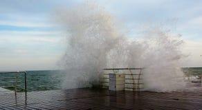 打破在停泊的波浪,形成浪花 波浪打破在风暴的海堤防 免版税库存图片