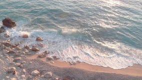 打破在多岩石的海滩的波浪空中寄生虫英尺长度在日落 股票录像