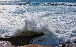 打破在岩石,悉尼,澳大利亚的打旋的太平洋波浪 图库摄影