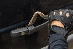打破在有撬杠工具的汽车锁的黑手套的匪盗 免版税图库摄影