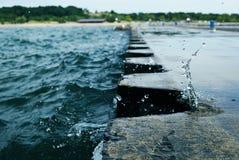 打破在有蓝色metall系船柱的跳船的波浪在密执安 免版税库存照片