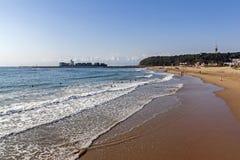 打破在海岸线和船输入的港口的海浪 库存照片