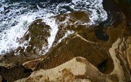 打破在海洋cliffside的波浪 免版税库存照片