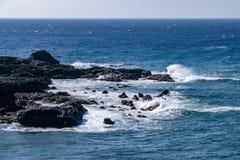 打破在熔岩荒野火山岩的边缘的波浪在Puerto de Naos,拉帕尔玛岛,加那利群岛 库存照片