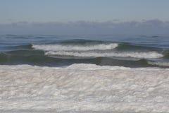 打破在零度以下的w的冰冷的密执安湖海岸线的波浪 免版税图库摄影