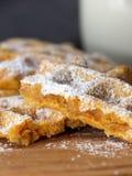 打破的红萝卜奶蛋烘饼拂去灰尘用在一个木板的糖粉在黑暗的背景 库存照片