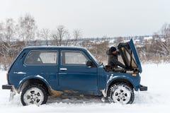 打破的蓝色俄国越野汽车Lada Niva 4x4华斯迪2121/21214停放与一顶开放帽子 库存照片