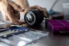 打破的透镜在与工具的修理桌,一个破裂的透镜,人修理照片设备的特写镜头上说谎 免版税库存图片