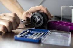 打破的透镜在与工具的修理桌,一个破裂的透镜,人修理照片设备的特写镜头上说谎 库存照片