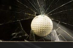 打碎球玻璃的高尔夫球 免版税库存照片