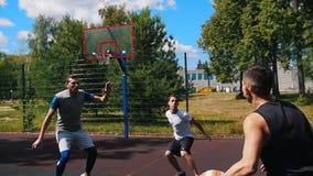 打篮球户外与朋友,滴下和trowing球的年轻运动员 股票录像