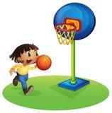 打篮球的一个小男孩 免版税库存照片