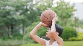 打篮球的少年亚裔男孩户外为射击做准备 免版税库存图片