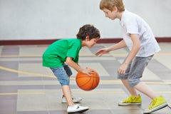 打篮球的男孩在学校 库存图片