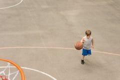 打篮球的年轻男孩跑与球 免版税库存照片