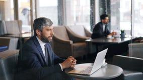 打网上视频通话的企业家使用膝上型计算机和无线耳机 股票录像